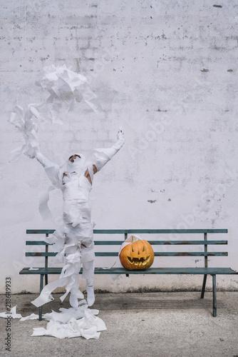 Fotografia  Little mummy boy with a pumpkin sitting in a street bench