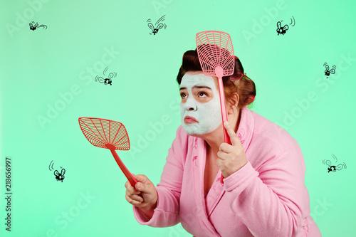 femme drôle en bigoudis et peignoir chassant des dessins de mouches