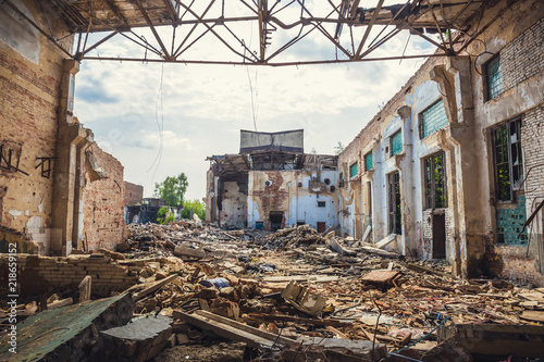 Fotomural Ruined abandoned industrial building with large pills of concrete garbage, after