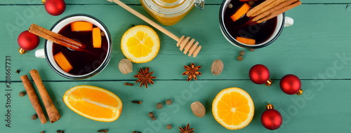Hot red mulled wine on wooden background with christmas spices, orange slice, anise and cinnamon sticks . Wide photo.