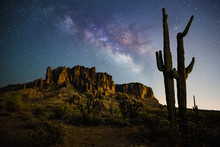 Milkyway Rising Behind The Superstition Mountains And Couple Saguaro Watching Together.