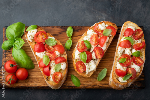Fototapeta Bruschetta with tomatoes, mozzarella cheese and basil on a cutting board. Traditional italian appetizer or snack, antipasto. Top view with copy space. Flat lay obraz