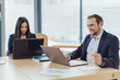 Businessman and woman sitting working on laptops