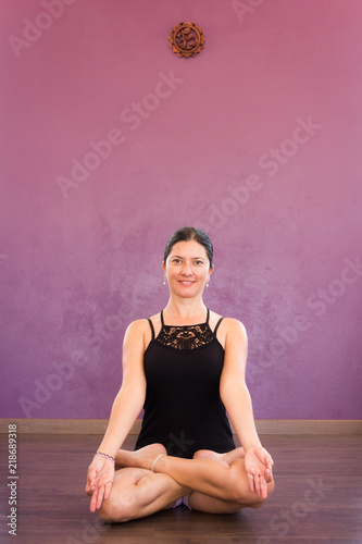 Beautiful yogi in padmasana. Smiling woman with black top practices lotus yoga pose. Young lady sitting with crossed legs with purple wall on background. Peaceful, mindfulness, meditation concepts