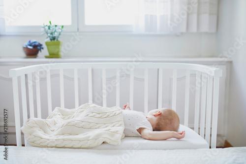 Photo Baby girl sleeping in co-sleeper crib
