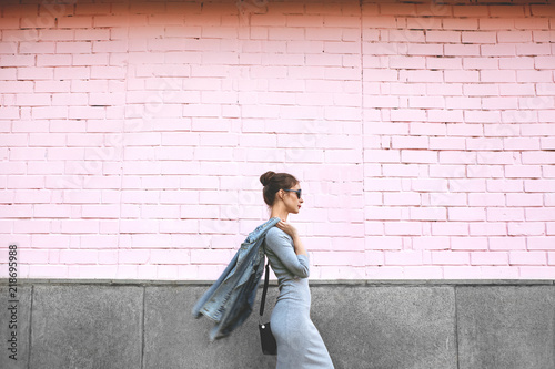 Obraz Street Style Shoot Woman on Pink Wall. Swag Girl Wearing Jeans Jacket, grey Dress, Sunglass. Fashion Lifestyle Outdoor - fototapety do salonu