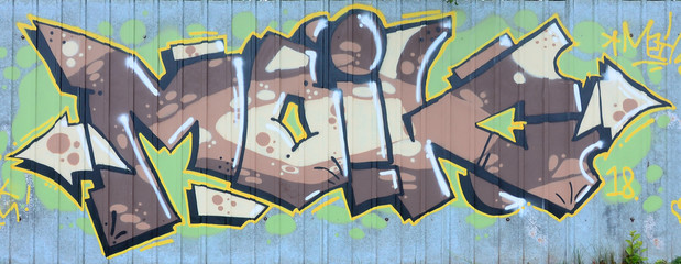 Full and acomplished graffiti artwork. The old wall decorated with paint stai...