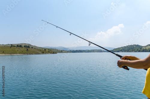 Fotografía  Unrecognizable man holding fishing rod next to beautiful lake on beautiful sunny