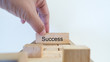 success word written on wood block with hand on white background