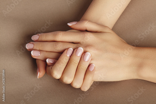 Poster Manicure Young Female Palm. Beautiful Glamour Manicure. French Style. Nail polish. Care about Hands and Nails, clean Skin