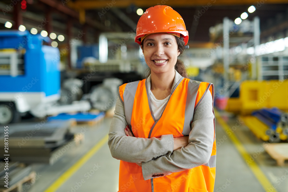 Fototapeta Waist up portrait of cheerful young woman wearing hardhat smiling happily looking at camera while posing confidently in production workshop, copy space