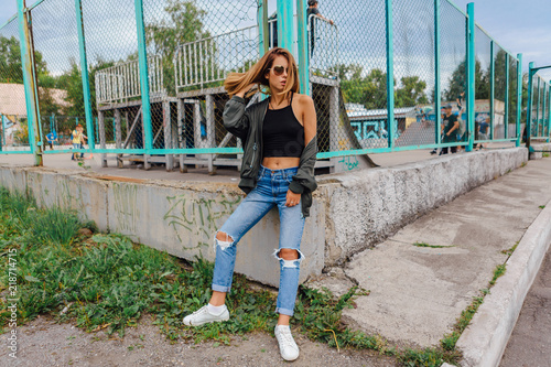 Foto Fashion portrait of trendy young woman wearing sunglasses, jeans with halls and