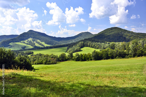 Foto op Canvas Blauwe hemel Beautiful summer landscape in the mountains with green meadows and forested hills, Low Beskids (Beskid Niski).