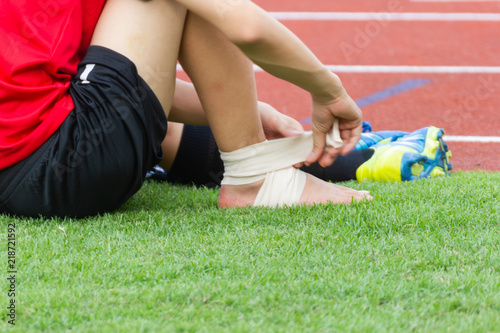 Photo man applying compression bandage onto ankle injury of a football player, Sports injuries