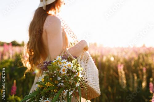 Fotografie, Obraz  Woman Walking Through Summer Field Carrying Bouquet Of Flowers in straw bag