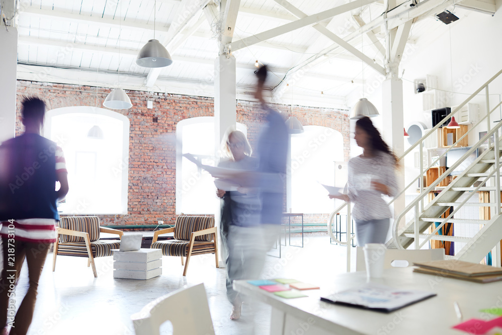 Fototapety, obrazy: Blurred motion of young business colleagues working in a busy open plan office