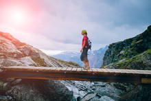 Young Woman Traveler With Backpacker And Bandana Going On Wooden Bridge In Cliff During Trip Norway. Trolltunga Hiking Route. Sunglare Effect. Forward To Goal Concept.