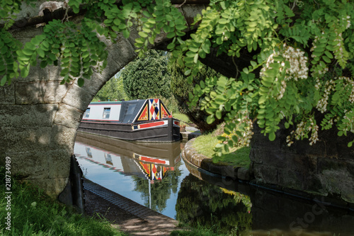 A close up view of the front part of a canal narrowboat. The view is taken through a old stone bridge and trees. The front of the leisure boat shows reflections in the water.