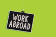Leinwanddruck Bild - Conceptual hand writing showing Work Abroad. Business photo text Immersed in a foreign work environment Job Overseas Non Local Hanging blackboard message communication sign green background.