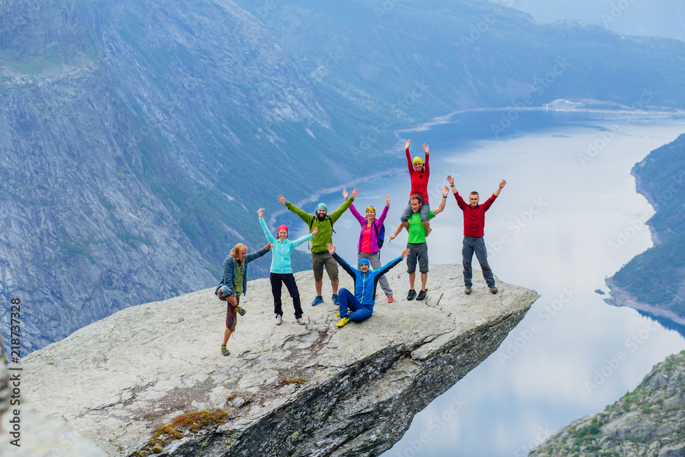 Fototapety, obrazy: Happy young sportive people group of eight in bright colorful sportswear have fun and enjoy in Trolltinga Norway mountain. Full body portrait
