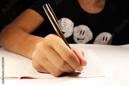 Tablou Canvas A young boy with black t-shirt writing dictation in english lesson