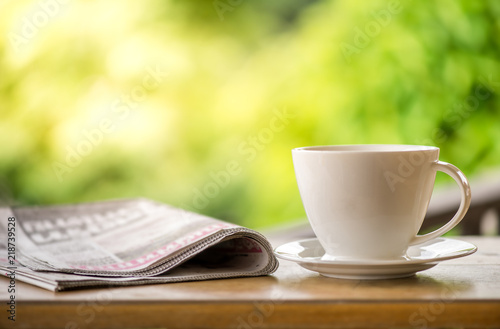 Cuadros en Lienzo good morning coffee cup with news paper on nature green background in garden
