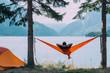 Leinwandbild Motiv Back view of man silhouette relaxing on orange hammock between two trees pine enjoying the view at the lake in summer norwegian cloudy morning.
