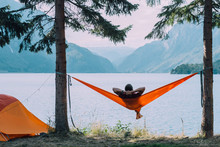 Back View Of Man Silhouette Relaxing On Orange Hammock Between Two Trees Pine Enjoying The View At The Lake In Summer Norwegian Cloudy Morning.
