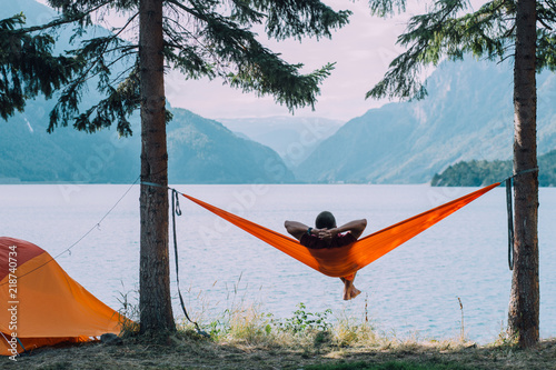 Fotografie, Obraz Back view of man silhouette relaxing on orange hammock between two trees pine enjoying the view at the lake in summer norwegian cloudy morning