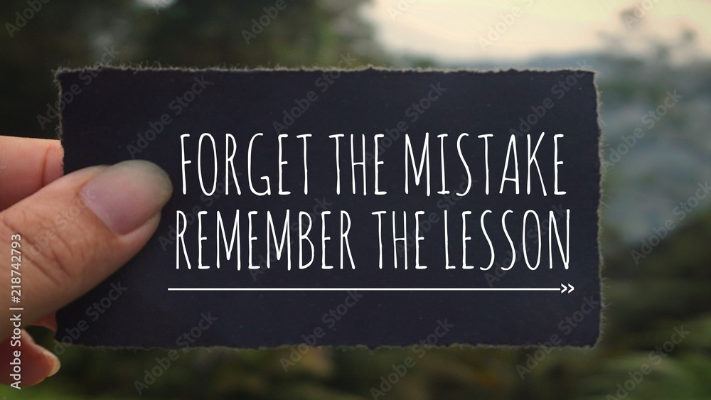Fototapeta Motivational and inspirational quote - 'Forget the mistake, remember the lesson' written on a black paper. Vintage styled background.