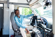smiling mature african american bus driver looking at camera while sitting inside bus