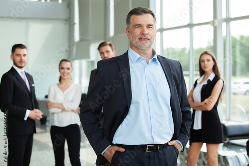 Fotomural Mature smiling business manager crossing his arms in front of his business team