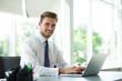 Leinwandbild Motiv Happy young businessman using laptop at his office desk