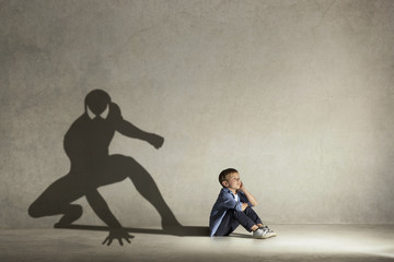 The little boy dreaming about hero figure with muscles. Childhood and dream concept. Conceptual image with boy and shadow of fit athlete on the studio wall