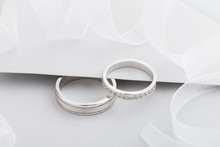 Two Silver Wedding Rings With Diamonds On Gray Background