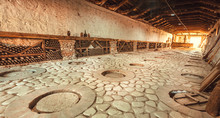 Huge Stone Cellar With Aged Dust Wine Bottles And Qvevri, Large Earthenware Vessels Under Ground. Rustic Farmhouse Interior With Rural Storage Of Winery.