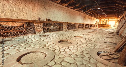 Fotografia  Huge stone cellar with aged dust wine bottles and qvevri, large earthenware vessels under ground