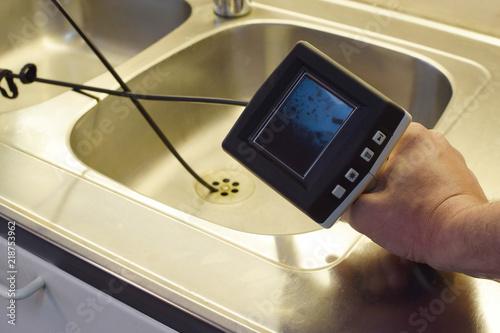 Pinturas sobre lienzo  Checking drain pipe with borescope inspection camera.