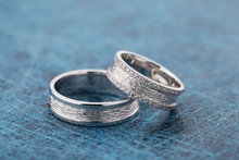 Two Textured Silver Wedding Rings On Blue Background