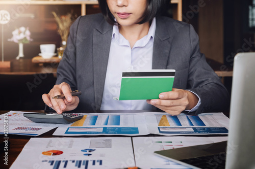 Saving and growth money concept bookkeeper using calculator, laptop computer and holding passbook to audit money account of her Canvas Print