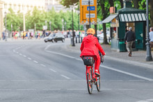 Woman In Red Rides A Bike At City Street, View From The Back