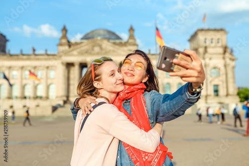 Fototapeta premium Dwa szczęśliwa kobieta robi selfie na tle Reichstag Bundestag budynek w Berlin. Koncepcja podróży i miłości w Europie