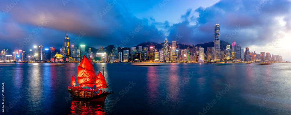 Fototapeta Panorama of Hong Kong City skyline with tourist sailboat at night. View from across Victoria Harbor HongKong.