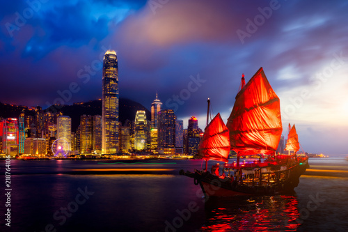 Poster Hong-Kong Hong Kong City skyline with tourist sailboat at night. View from across Victoria Harbor Hong Kong.