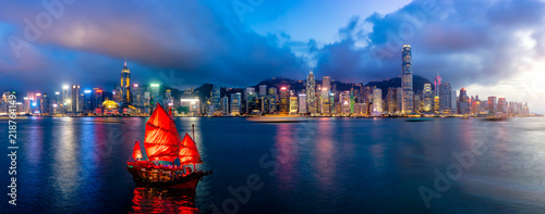 Poster Hong-Kong Panorama of Hong Kong City skyline with tourist sailboat at night. View from across Victoria Harbor HongKong.