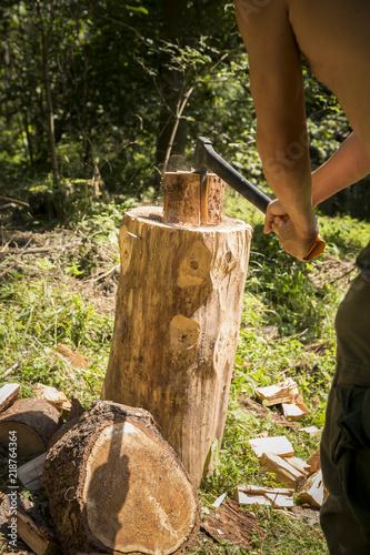 rąbanie siekierą drwa na opał w lesie