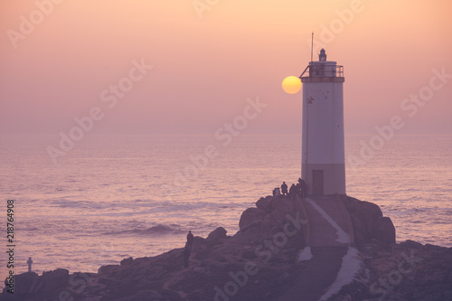 Foto auf Leinwand Leuchtturm People watching ocean sunset. Roncudo Lighthouse at Spain