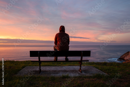 Pinturas sobre lienzo  Lonely man sits alone on the rocky coast and enjoying sunset