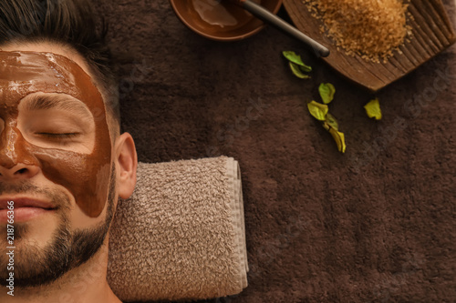 Photo  Young man with face mask on massage table in spa salon