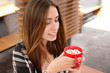 Beautiful young woman with cup of sweet cocoa drink in cafe